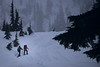 Whatcom, Artist Point - Two snowshoers walking up a snowy hill in a snowstorm