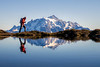 Whatcom, Yellow Aster Butte - Hiker passing small tarn with Mt. Shuksan reflected