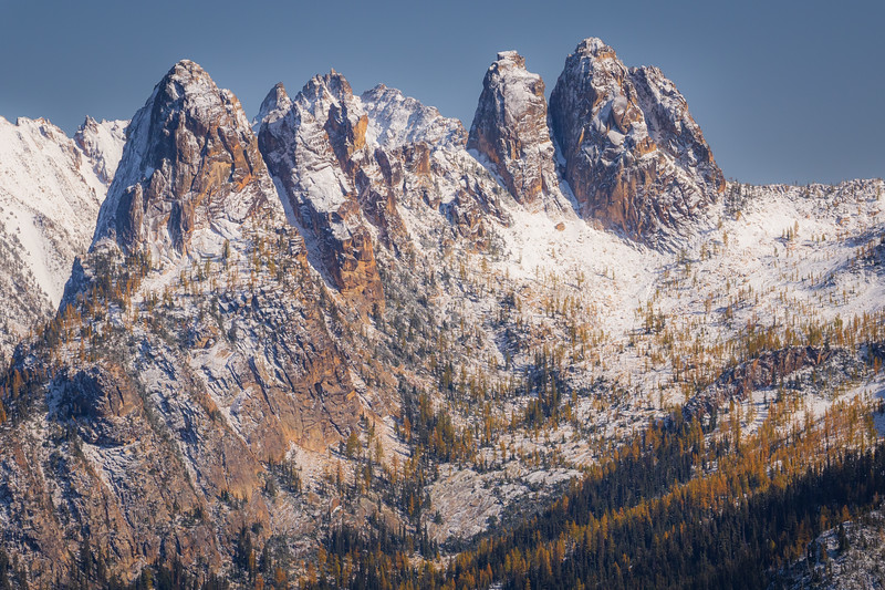 Rainy Pass. Maple Pass - Liberty Bell group in the snow above a larch forest