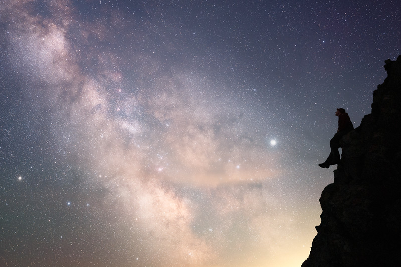 Whatcom, Artist Point - Man sitting on edge of cliff looking at Milky Way