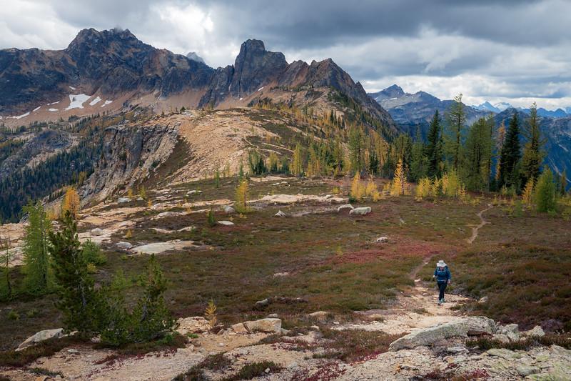 Rainy Pass, Cutthroat Pass - Woman hiker ascending meadows above Cutthroat Pass with Cutthroat Peak in distance