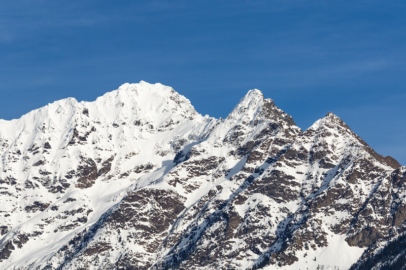 North Cascades, Ross Lake - Top of snow covered peak in blue sunshine