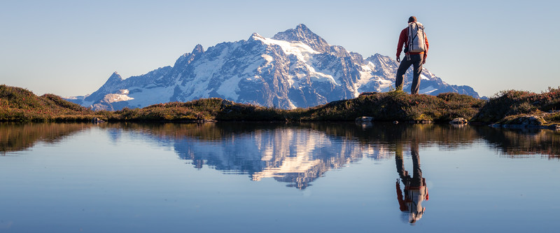 Whatcom, Yellow Aster Butte - Hiker pausing to look at Mt. Shuksan reflected in tarn, panoramic