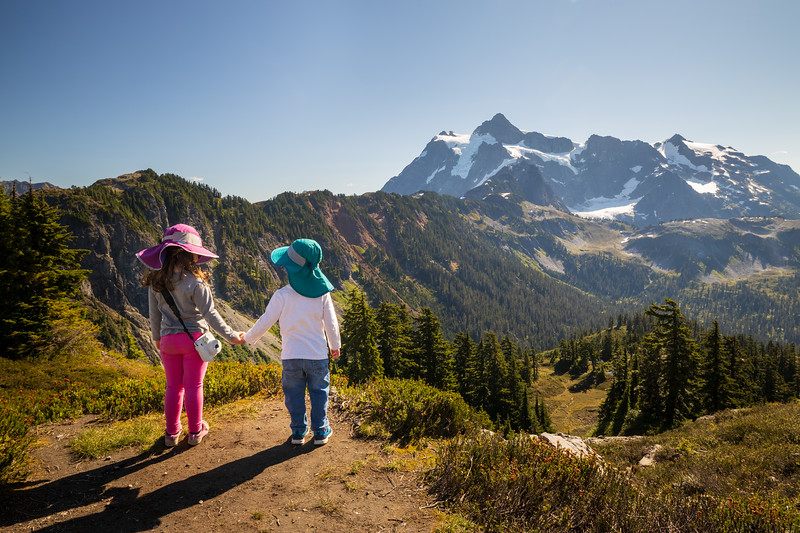Whatcom, Artist Point - Two little kids holding hands and looking at each other, overlooking a valley and Mt. Shuksan