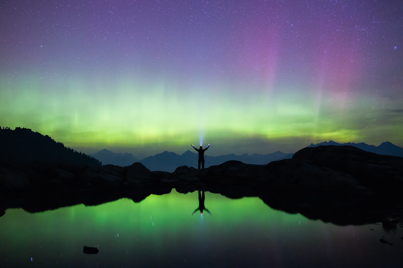 Whatcom, Artist Point - Man standing with arms up next to lake with colorful aurora