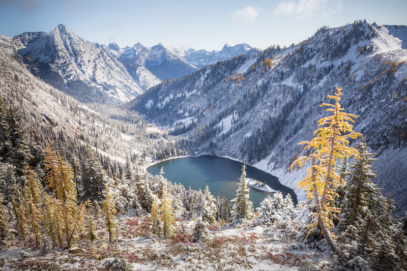 Rainy Pass. Maple Pass - Lake Ann in a snow-covered valley with fall colors and small, bright larch in foreground