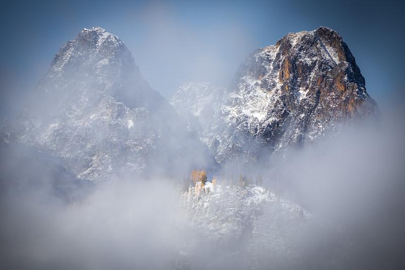 Rainy Pass. Maple Pass - Small stand of larch peeking through the fog beneath two imposing peaks