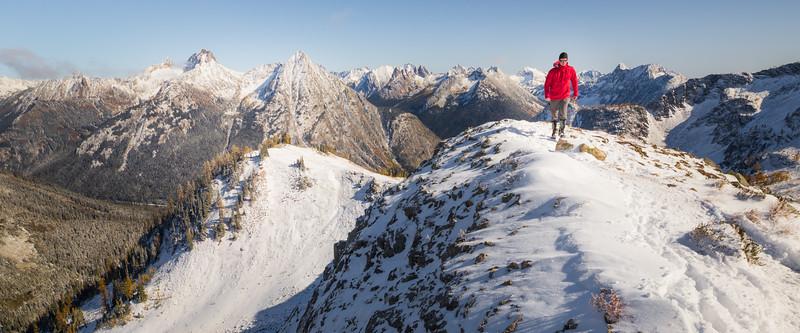 Rainy Pass. Maple Pass - Man in red jacket walking along snowy ridge towards camera, view towards Washington Pass, tighter crop