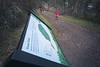 Skagit, Kukutali Preserve - People walking up a trail with only foreground sign in focus