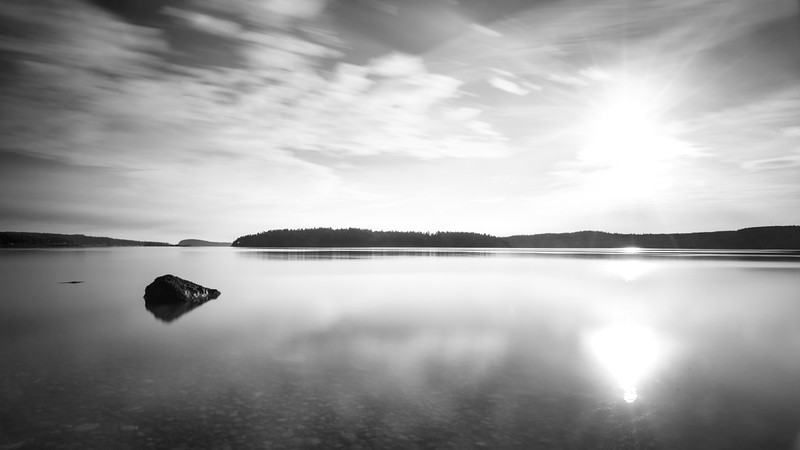 Skagit, Kukutali Preserve - Long exposure seascape with rock and sun, black and white