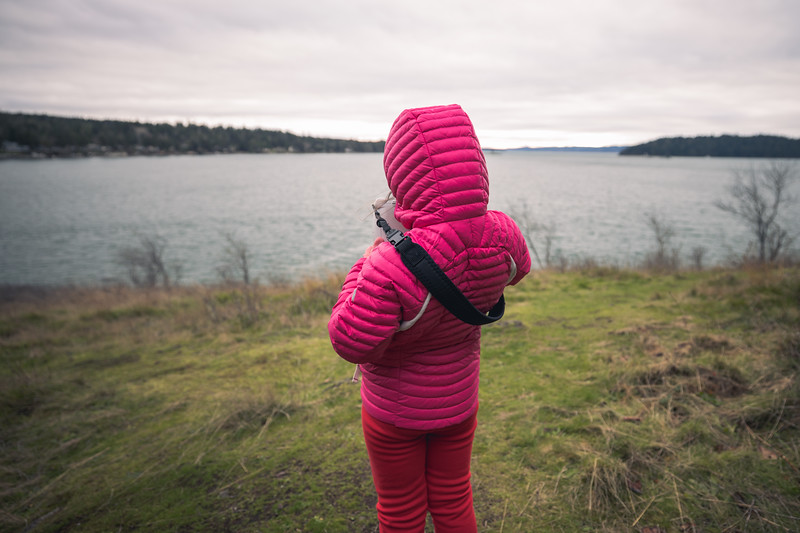 Skagit, Kukutali Preserve - Little girl with instant camera taking picture of the view