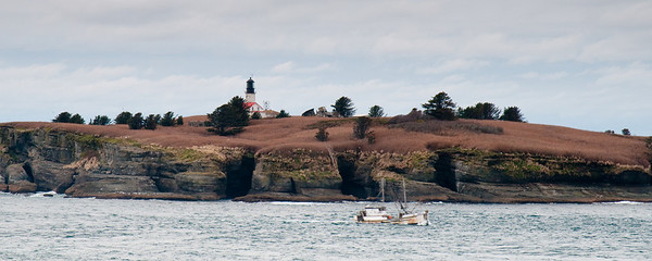Fishing boat passing in front of Cape Flattery lighthouse