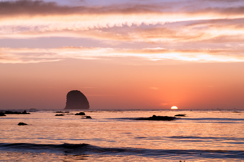 Olympic NP, Ozette Coast - Seastack and setting sun halfway over the horizon