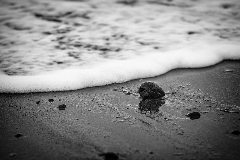 Sequim, Dungeness Spit - Small rock on shore with advancing wave, black and white
