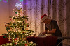 North Seattle, Indoors - Man ironing with Santa hat next to Christmas Tree