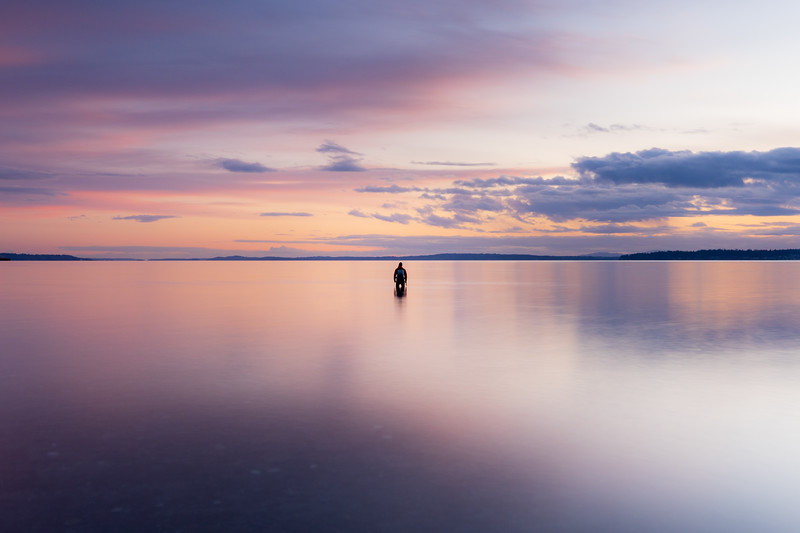 Edmonds, Marina Beach Park - Small man standing in calm water with colorful sunset