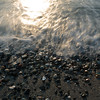 Mukilteo, Beach - Waves coming on shore with pebbles and sun glint