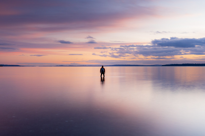 Edmonds, Marina Beach Park - Man standing in calm water with colorful sunset