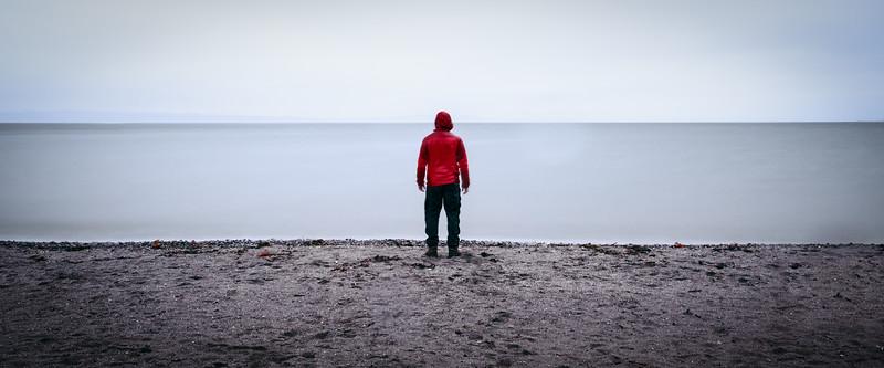 Seattle, Carkeek - Man standing along featureless shoreline in the rain