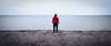 Seattle, Carkeek - Man standing along featureless shoreline in the rain