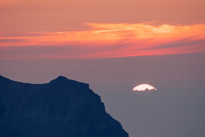 Rainier, Sunrise - Wispy clouds and setting sun silhouetting peaks of the Olympic Mountains