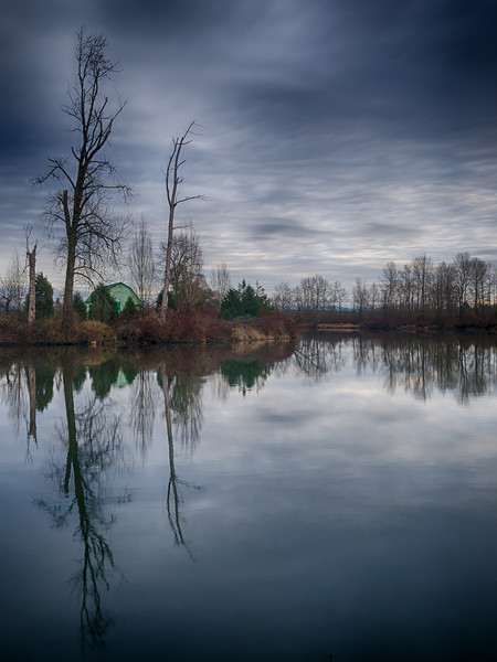 Everett, Lowell Riverfront - Green barn on the shore of the Skykomish River on a cloudy day