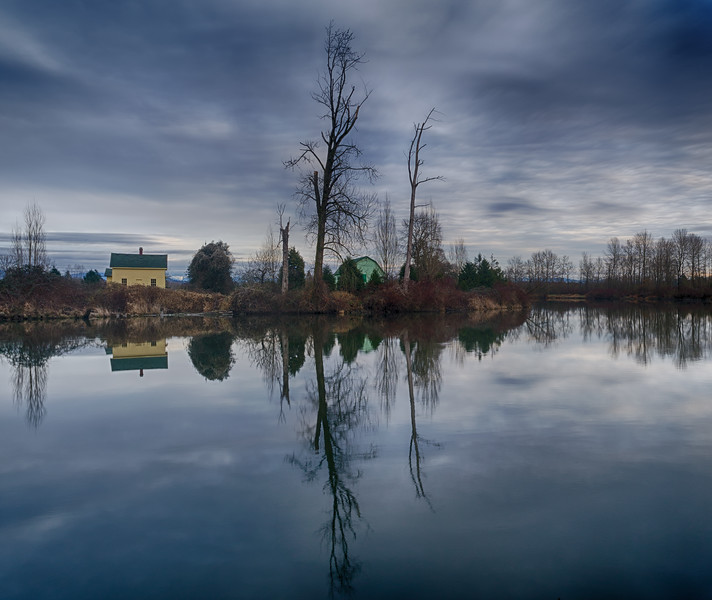 Everett, Lowell Riverfront - Yellow and green barns on the shore of the Skykomish River on a cloudy day, wide