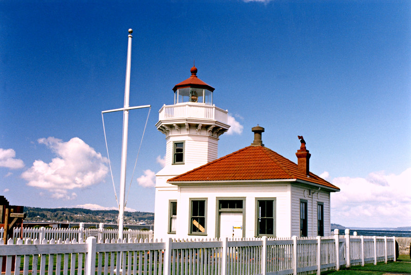 At the turn of the century the Lighthouse Board decided a light was needed to mark Elliot Point, but had some trouble obtaining the land from the owner. Eventually, 2.6 acres were obtained and a 38 foot tall Victorian tower of fir wood was constructed in 1906. The plans used were a Carl W. Leick design that was also used for the Ediz Hook lighthouse and the second light at Cape Arago, Oregon.