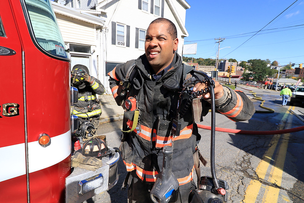. As the Fitchburg Fire Department battled a fire at 114 and 116 Laurel Street a water main broke and water started rushing down the street. Fitchburg Fire Lt.Robert DaCosta takes off his gear after helping to fight the fire. SENTINEL & ENTERPRISE/JOHN LOVE