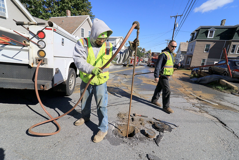 As the Fitchburg Fire Department battled a fire at 114 and 116 Laurel Street a water main broke and water started rushing down the street. Employees of the Water Department Miguel Valencia and Forman Greg Leger work on turning of the water. SENTINEL & ENTERPRISE/JOHN LOVE