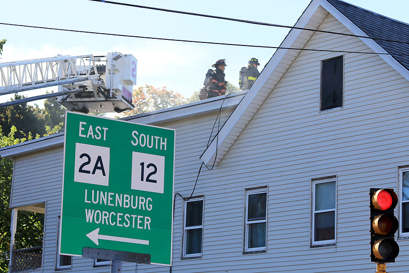 As the Fitchburg Fire Department battled a fire at 114 and 116 Laurel Street a water main broke and water started rushing down the street. Firefighter fight the fire from the roof. SENTINEL & ENTERPRISE/JOHN LOVE