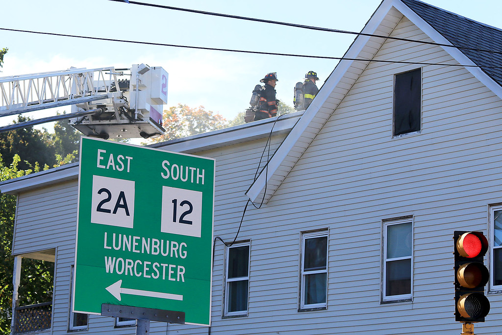 . As the Fitchburg Fire Department battled a fire at 114 and 116 Laurel Street a water main broke and water started rushing down the street. Firefighter fight the fire from the roof. SENTINEL & ENTERPRISE/JOHN LOVE