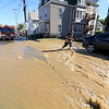 As the Fitchburg Fire Department battled a fire at 114 and 116 Laurel Street a water main broke and water started rushing down the street. A firefighter walks through the water that was rushing down the street. SENTINEL & ENTERPRISE/JOHN LOVE