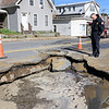 As the Fitchburg Fire Department battled a fire at 114 and 116 Laurel Street a water main broke and water started rushing down the street. Fire Chief Kevin Roy looks into the hole now in the street caused by the water main brake. SENTINEL & ENTERPRISE/JOHN LOVE