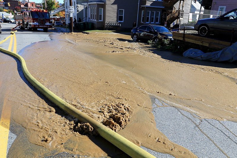 As the Fitchburg Fire Department battled a fire at 114 and 116 Laurel Street a water main broke and water started rushing down the street. SENTINEL & ENTERPRISE/JOHN LOVE