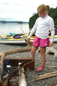 At camp on Pelican Beach on Cypress Island, Laura gets another marshmallow over the fire while still chewing.