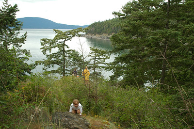 Laura ducks down low while Natalie walks out to where Maria has perched herself to take in the scene of the San Juan Islands as seen from the north side of Strawberry Island.