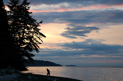 David works his way down the beach skipping rocks on Pelican Beach, Cypress Island at sunset.