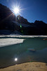 The shining sun reflects off Upper Grinnell Lake in Glacier National Park.