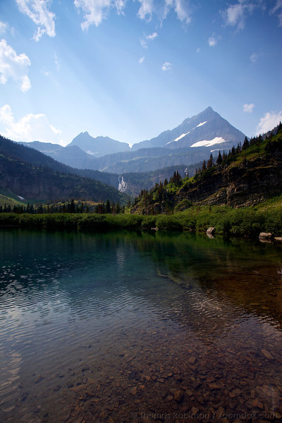 Cathedral Peak, on the continental divide, stands high above Atsina Lake in Glacier National Park. Atsina Falls can also be seen coming off the basin below Sue Lake.