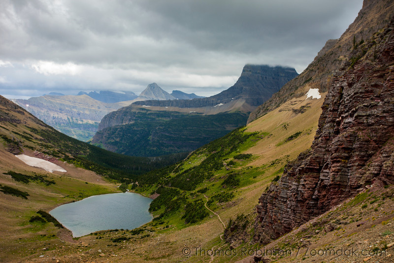 The view from Ptarmigan Tunnel looks over the trail around Ptarmigan Lake down to Mount Wilbur and Mount Grinnell. An epic landscape to behold with red rock and jagged mountain spires.