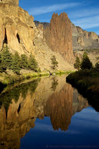 The Smith Rock Palisade towers above the Crooked River, reflected in the golden light of sunset.