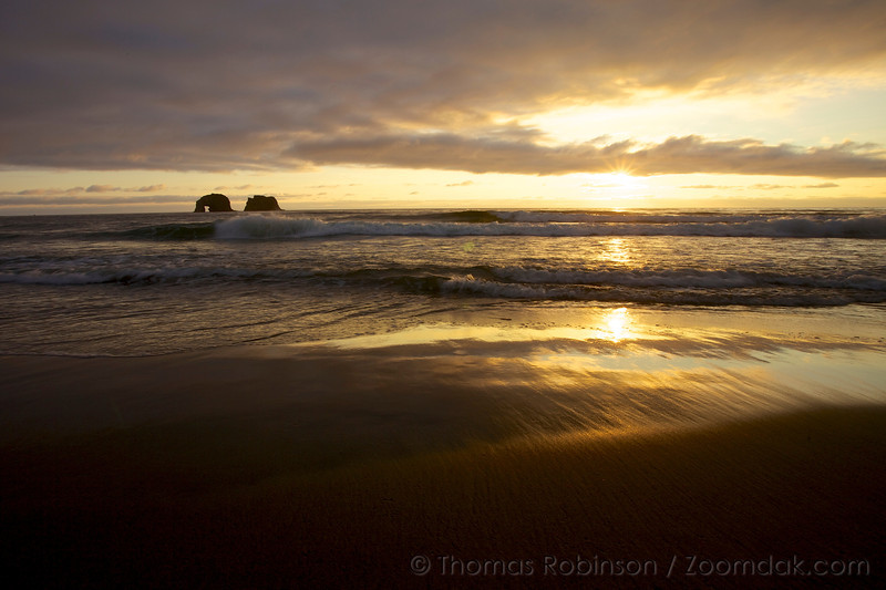 Sunset over the Pacific Ocean with Twin Rocks silhouetted in the background in Twin Rock State Park, Rockaway Beach, Oregon