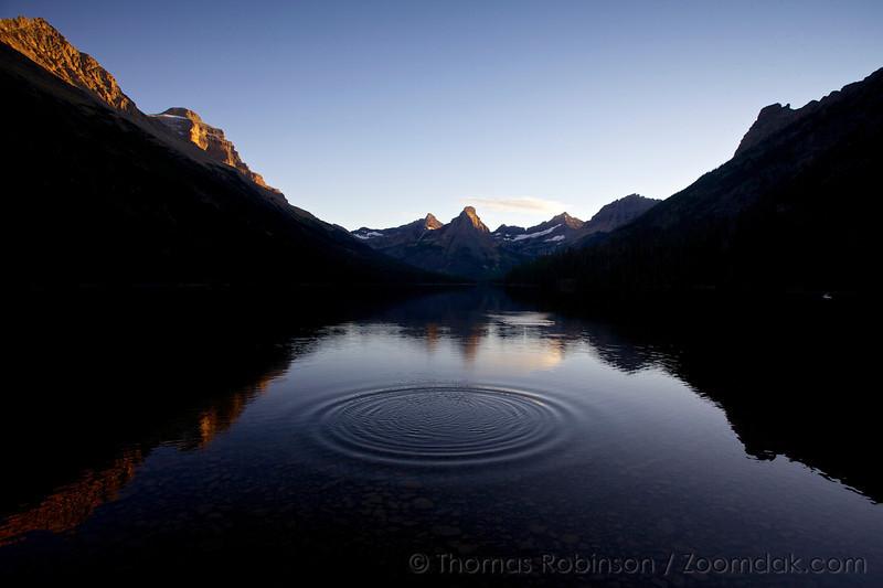 A rock skip creates concentric circles on Glenns Lake at sunset in Glacier National Park, Montana.