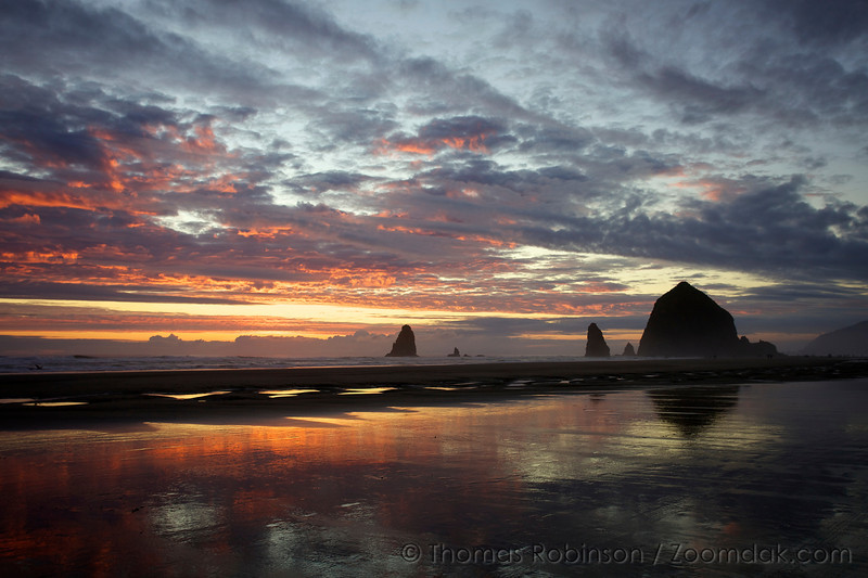The tips of clouds catch the last rays of the day above Haystack Rock in Cannon Beach, Oregon.