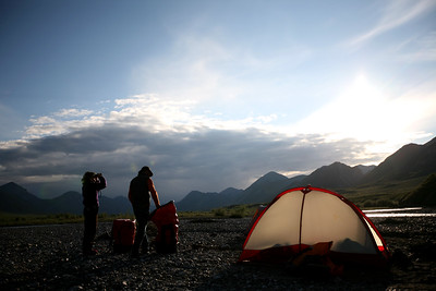 KONGAKUT RIVER, AK - Camp I: Headwater. Lindsay scans the hillside to the north for animals in the arctic midnight sun.