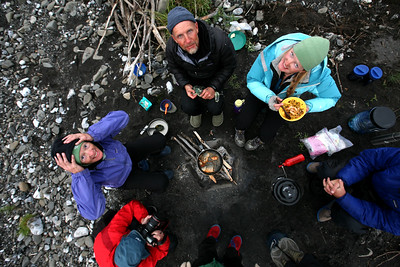 KONGAKUT RIVER, AK - Camp III: Drain Creek; Gathered around the cooking campfire.