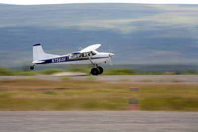 ARCTIC VILLAGE, AK - A Cessna 185 with tundra tires lands on the gravel airstrip.