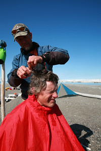 KONGAKUT RIVER, AK - Camp IX: Icy Reef; Fourth of July celebrations start with carving a mullet out of Nathaniels poofy hair. Bobby uses sissors from his first aid kit.