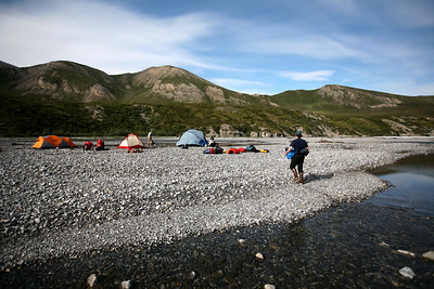 KONGAKUT RIVER, AK - Camp I: Headwater. Nathaniel carries one of the inflateable kayaks (ducky) from the last of three flights into our first camp about 16 river miles above Drain Creek where the commercial guide services start their trip.